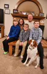 Sheri and Dan Haus pose for a photo with sons Cole, Brady and Ethan and the family dog Remington Tuesday, Dec. 10, in their home near Clear Lake.