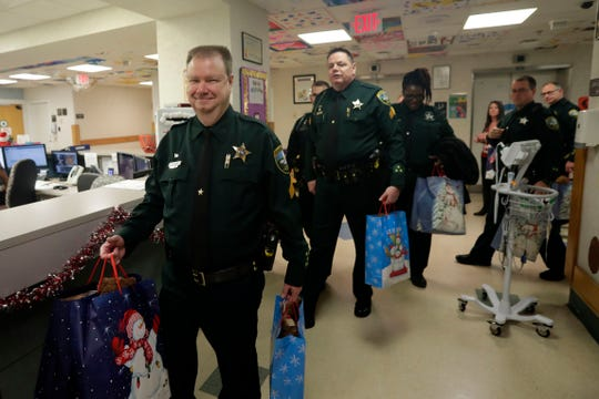 Officers with the Leon County Sheriff's Office carry bags filled with teddy bears and quilts, which they will deliver to pediatric patients.