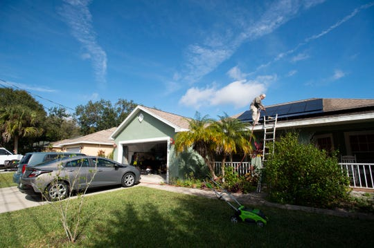 """Jerry Buechler, of Port St. Lucie, cleans the 28 solar panels on his roof Wednesday, Dec. 4, 2019, in Port St. Lucie. Buechler has converted his 4-bedroom, 3-bathroom house to completely run off solar energy and also drives an electric vehicle and uses an electric lawn mower. He formed the Treasure Coast Solar Co-op with fellow retired Miami Beach firefighter Richard Silvestri after seeing streets in Miami Beach flooding on sunny days and watching the city spend over $500 million raising streets and putting in pumps. """"It's a short-term solution to a long-term problem. The only real solution... is to reduce our carbon footprint,"""" Buechler said."""