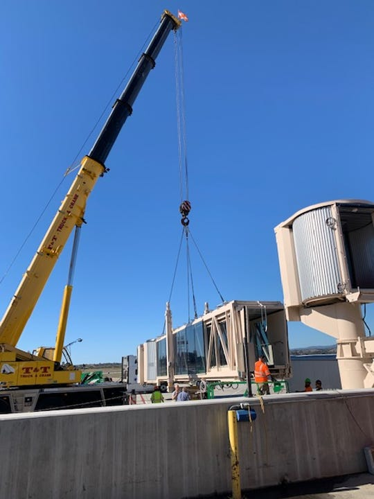 A new passenger jet bridge is hoisted into place at the Santa Barbara Airport. The glass-and-steel construction is uncommon.