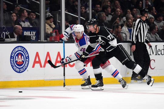 Dec 10, 2019; Los Angeles, CA, USA; Los Angeles Kings center Jeff Carter (77) and New York Rangers left wing Chris Kreider (20) battle for the puck in the first period at Staples Center.