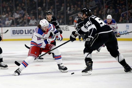 New York Rangers' Artemi Panarin, left, is defended by Los Angeles Kings' Kurtis MacDermid (56) during the first period of an NHL hockey game Tuesday, Dec. 10, 2019, in Los Angeles.