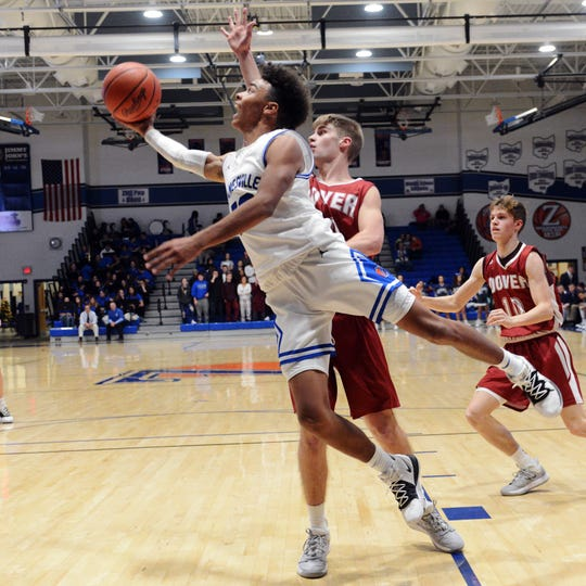 Isaac Mayle makes a move on Ayden Hall along the baseline during the first half of Zanesville's 58-27 loss to visiting Dover on Tuesday night at Winland Memorial Gymnasium.