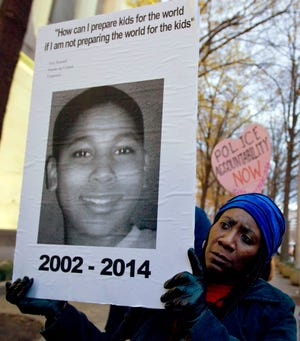 Tomiko Shine holds up a picture of Tamir Rice during a protest this winter in Washington, D.C.