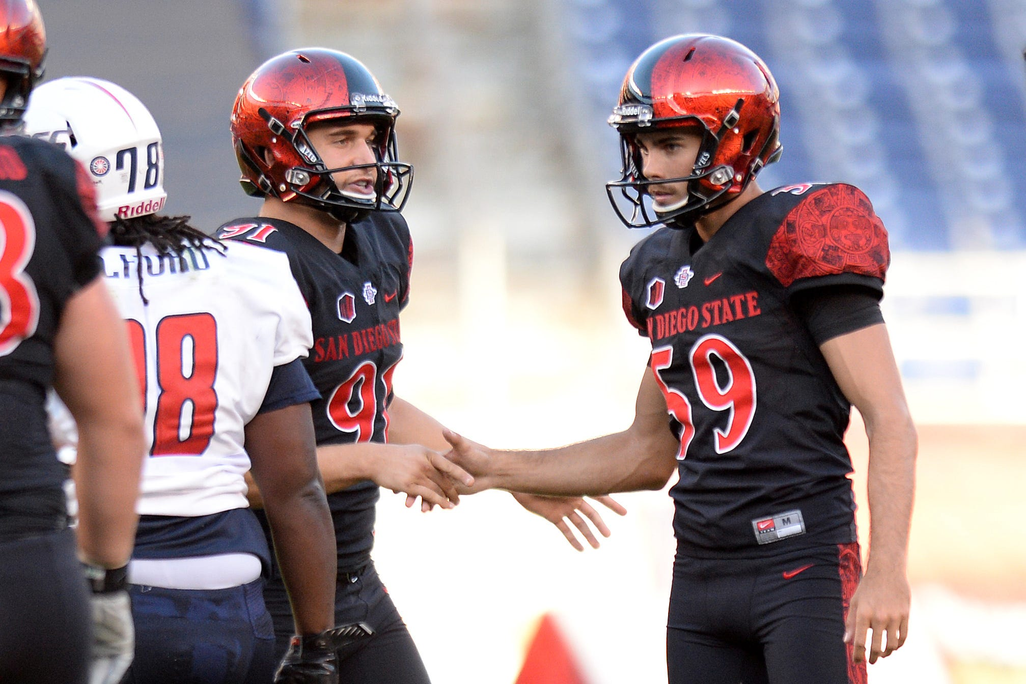 San Diego State Aztecs punter Tanner Blain (91) congratulates place kicker Donny Hageman (59) after Hageman made a field goal during the second quarter against the South Alabama Jaguars at Qualcomm Stadium on Sep 19, 2015.