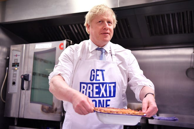 Britain's Prime Minister Boris Johnson prepares a pie at the Red Olive kitchen in Derby, England, on the final day of campaigning before a general election on Dec. 12, 2019.  in Derby, England.