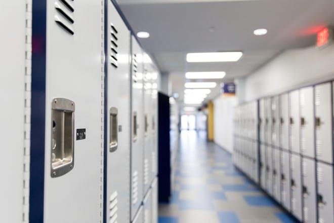 Lockers line empty hallway in school building.