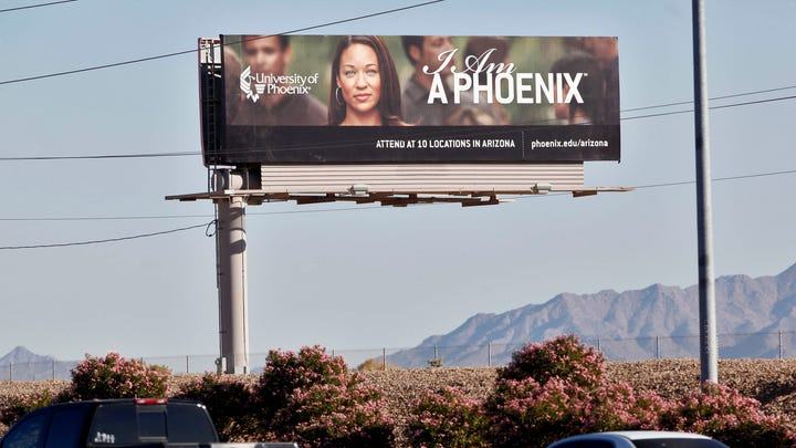 In this Nov 24, 2009, file photo, a University of Phoenix billboard is shown in Chandler, Ariz. The University of Phoenix for-profit college and its parent company will pay $50 million and cancel $141 million in student debt to settle allegations of deceptive advertisement brought by the Federal Trade Commission.