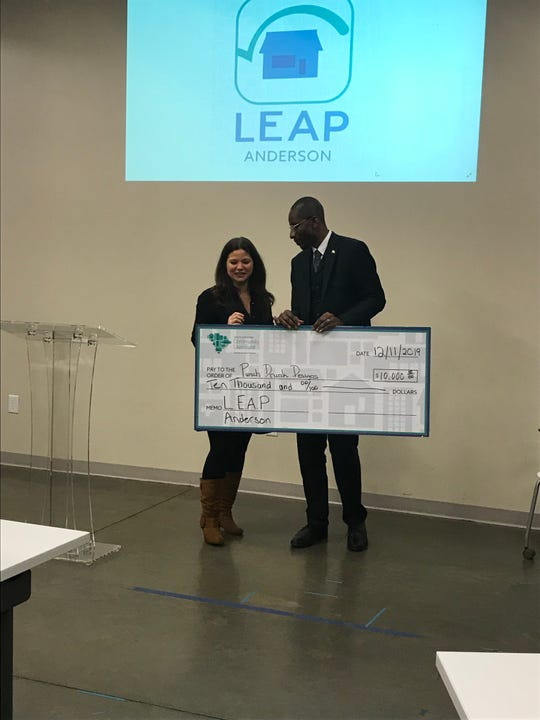 James Chatfield, of the South Carolina Community Loan Fund, awards  Whitney Farmer Black with a $10,000 check at LEAP Anderson pitch night Wednesday, Dec. 11. Black's business is a make-and-take art class space near downtown Anderson.