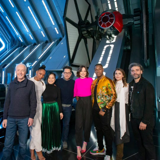 """In this handout photo provided by Disney Resort, the cast of the upcoming film """"Star Wars: The Rise of Skywalker,"""" from left, Anthony Daniels, Naomi Ackie, Kelly Marie Tran, director J.J. Abrams, Daisy Ridley, John Boyega, Keri Russell and Oscar Isaac, gets a first-look at the new Star Wars: Rise of the Resistance attraction in Star Wars: Galaxys Edge at Disneyland Park December 2, 2019 in Anaheim, California."""