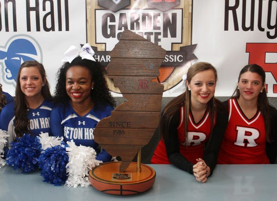 Rutgers and Seton Hall cheerleaders pose with the Boardwalk Trophy in 2014.