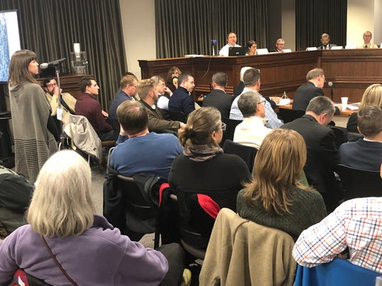 Karalyn Warren, at the microphone, testifies Dec. 11 at the Board of Adjustment hearing about the Crossroads at West Asheville project. Warren said her property will be adversely affected by the apartments, if built.