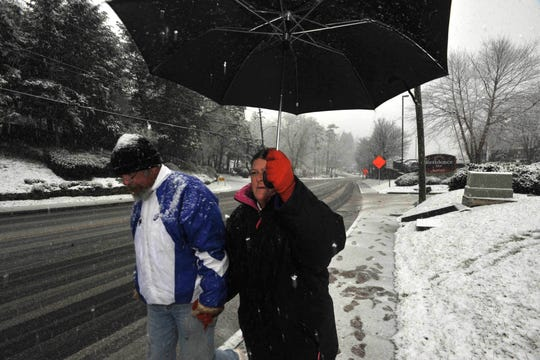 """Dave Hill and Kim Cook make their way up Biltmore Avenue as the snow begins to take hold Friday afternoon.""""This is miserable,"""" commented Hill on the second big snowstorm this season. Jan. 29, 2010"""