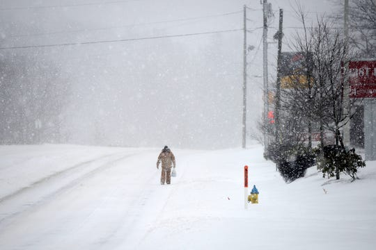 A man walks in tire tracks in the road because the sidewalks were covered as he makes his way down New Leicester Highway in the snow on Friday, Jan. 22, 2016.