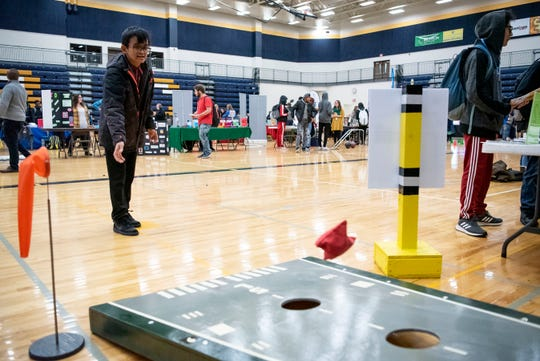 Battle Creek Central freshman Tun Kham plays cornhole at the Battle Creek Executive Airport table during the Career Exploration Fair on Thursday, Dec. 12, 2019 at Battle Creek Central High School in Battle Creek, Mich.