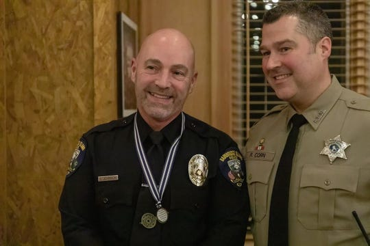 Bainbridge Island Officer Dale Johnson, left, and Kitsap County sheriff's Deputy Rob Corn, right, are shown after Johnson was awarded the department's medal of valor award for his actions in the shooting of Brandon Roberts. A jury acquitted Roberts of assaulting Johnson. Roberts pleaded guilty last week to a misdemeanor assault on Corn.