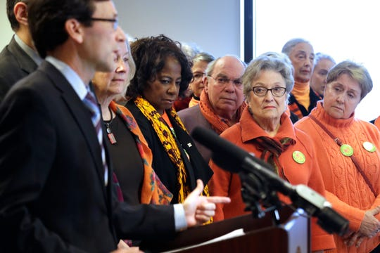 Members of Grandmothers Against Gun Violence look on as Washington state Attorney General Bob Ferguson addresses a news conference announcing legislation to combat mass shootings in the state on Thursday.