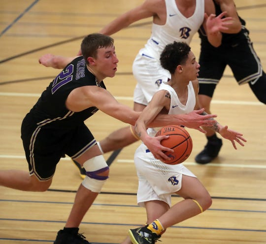 North Kitsap's Logan Chmielewski (21) makes a grab for the ball as Bremerton's D'Angelo T. Moore dribbles down the court on Wednesday, December 11, 2019.