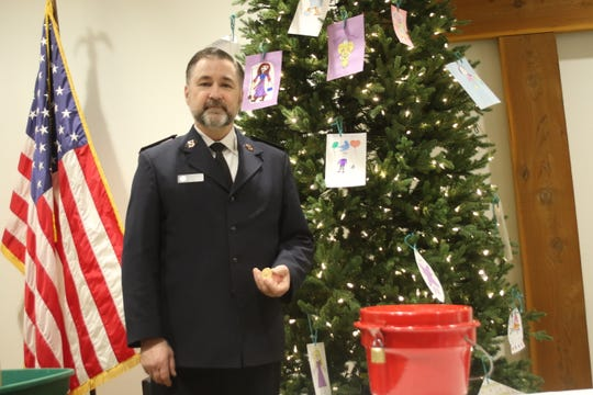 Captain Lance Walters, director of the Bremerton Salvation Army, holds a $1,500 gold coin dropped this week in a red kettle.