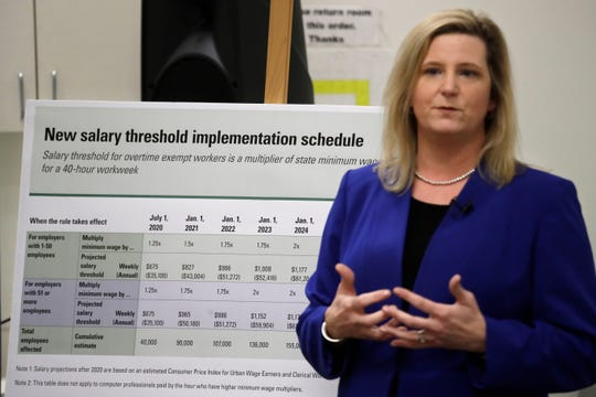 Washington state Labor and Industries Deputy Director Elizabeth Smith talks about new overtimes rules during a news conference Wednesday, Dec. 11, 2019, in Tukwila.