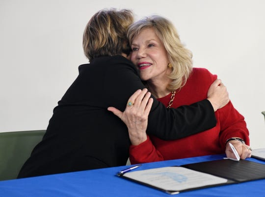 Texas A&M-Corpus Christi president Kelly Quintanilla, left, hugs Janet Maxwell during a ceremonial signing of the documents for their acquirement of her and her husband's building, Thursday, Dec. 12, 2019. The university paid $2.3 million for the 77,000-square foot building.