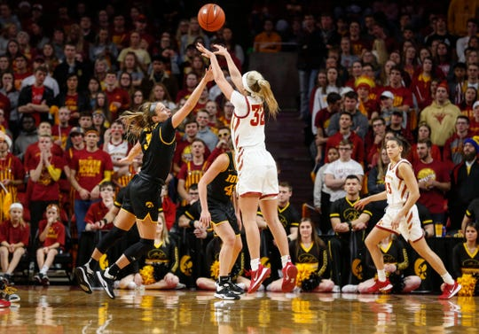 Iowa State freshman Maggie Espenmiller-McGraw launches a three-point shot over the reach of Iowa senior Makenzie Meyer in the first quarter during the CyHawk Series women's basketball game on Wednesday, Dec. 11, 2019, at Hilton Coliseum in Ames, Iowa.