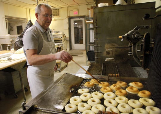 Gary Martinson flips doughnuts in the fryer at Hiland Bakery. Tracy Adamson has bought the business and says she will reopen it soon.