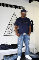 Michael Locke is pictured wearing a shirt and accessories from his clothing line, IAMHIMHEISI.