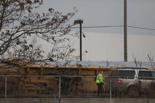 A member of law enforcement walks by a derailed train on its side in southwest Detroit Thursday, Dec. 12, 2019.