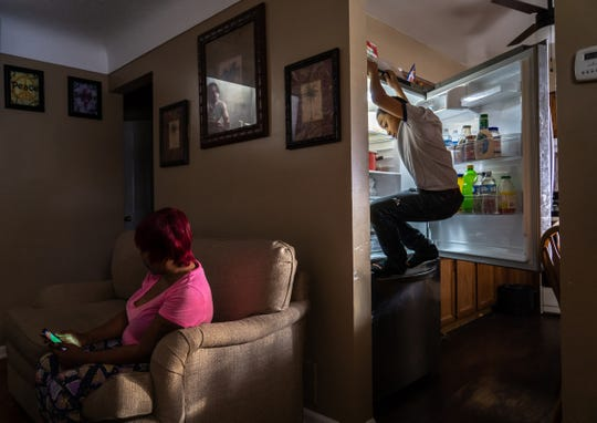Jaylon Tyson, 11, of Flint climbs on the refrigerator to get an item while preparing food as his mother Nakiya Wakes sits on the the couch of their home on Flint's north side on Wednesday, December 11, 2019.Nakiya homeschools her son, who was diagnosed with ADHD and developed a tic at age 5, after she says that officials told her they were unable to handle him and he was repeatedly suspended.Nakiya says the exposure to the Flint water caused her to lose twins and having her son's issues after having him tested to find high levels of lead in his body.