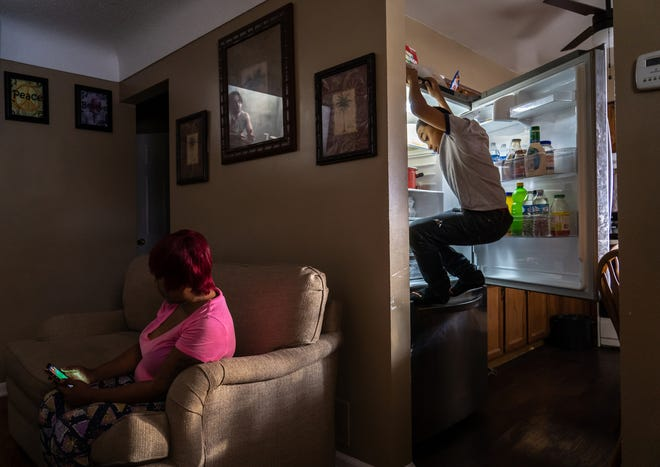 Jaylon Tyson, 11, of Flint climbs on the refrigerator to get an item while preparing food as his mother Nakiya Wakes sits on the the couch of their home on Flint's north side on Wednesday, December 11, 2019.