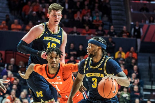 Michigan's Zavier Simpson works with the ball around the defense of Illinois' Trent Frazier as Michigan's Jon Teske stands by in the second half of U-M's 71-62 loss on Wednesday, Dec. 11, 2019, in Champaign, Ill.