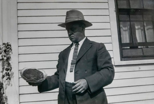 Lyman Hezekiah Ford, grandson to Fidelia Ford, holds the fruitcake during its 50th year in 1928.