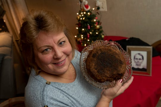 Julie Ruttinger, of Tecumseh, holds a 141-year-old fruitcake, a family heirloom baked by her great -great grandmother Fidelia Ford, in 1878.
