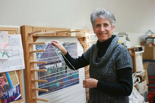 Carol Irving prepares a warp for her loom in her studio.