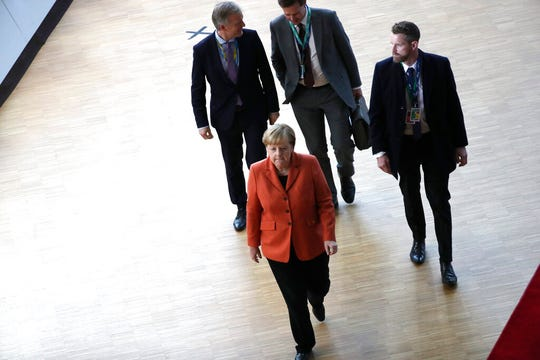 German Chancellor Angela Merkel, second left, arrives for an EU summit in Brussels, Thursday, Dec. 12, 2019.