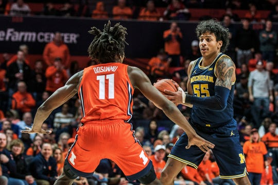 Michigan's Eli Brooks looks to pass as Illinois' Ayo Dosunmu defends in the second half.