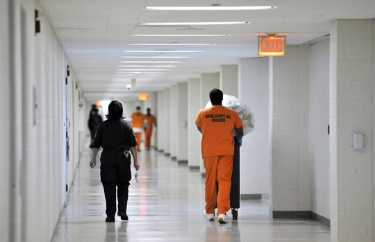 A sheriff's corporal escorts an inmate worker in a long hallway in the jail.