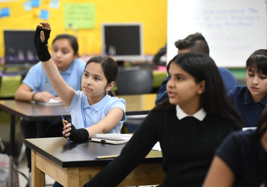 Clippert Multicultural Magnet Honors Academy student Ashley Azpetia raises her hand to answer a questions with fellow student Haneen Duais, right,  during teacher Tracy Ortiz's program to engage students in real world activities off campus.