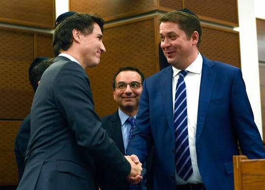 Prime Minister Justin Trudeau, left, shakes hands with Conservative Leader Andrew Scheer after his remarks at Hanukkah on the Hill celebrations in Ottawa, Ontario, Monday, Dec. 9, 2019.