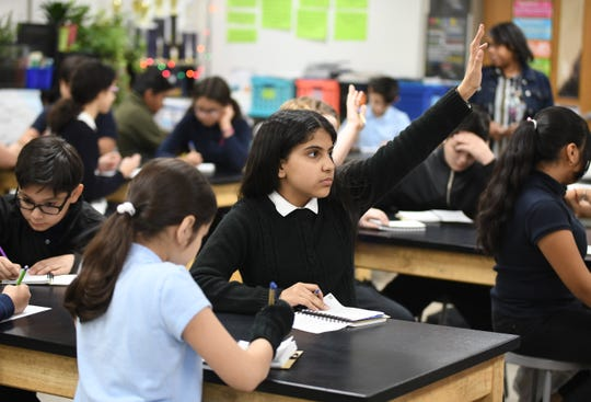 Clippert Multicultural Magnet Honors Academy student Haneen Duais (center) is eager to answer a question during teacher Tracy Ortiz's program to engage students in real world activities off campus.