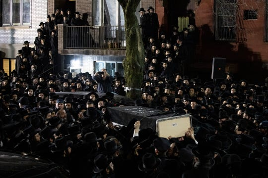 Orthodox Jewish men carry Moshe Deutsch's casket outside a Brooklyn synagogue following his funeral, Wednesday in New York.
