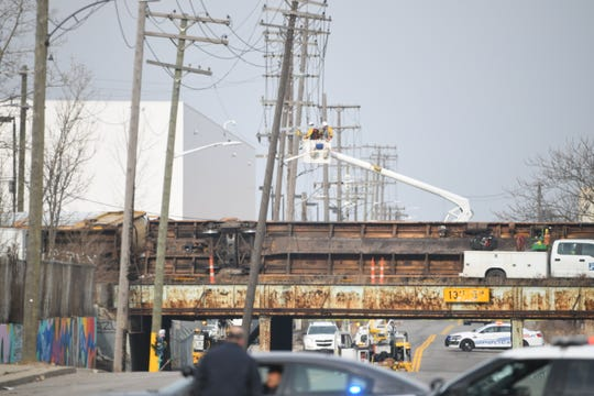 An overturned rail car lies on its side at the overpass on Scotten Avenue in Southwest Detroit Thursday morning after a train derailed.