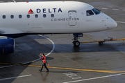 A ramp worker guides a Delta Air Lines plane at Seattle-Tacoma International Airport in Seattle.