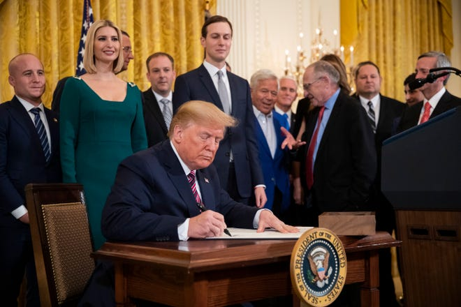 President Donald Trump signs an executive order combatting anti-Semitism in the U.S. during a Hanukkah reception in the East Room of the White House Wednesday, Dec. 11, 2019, in Washington.