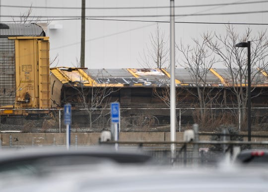 A derailed train car leans off the tracks in Southwest Detroit Thursday morning.