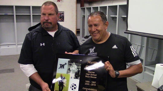 Mariner athletic director Steve Larsen presents Triton soccer coach Martin Cardenas with a plaque commemorating his 400th career coaching win achieved Dec. 9 against Barron Collier.
