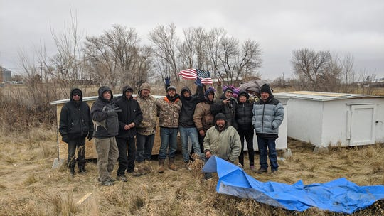 People experiencing homelessness in Fort Peck  gather around some of Johannessen's sleeping huts.