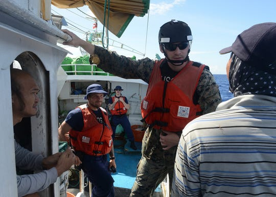 A marine law enforcement boarding team from the Coast Guard Cutter Washington conducts an at sea inspection of a fishing vessel off the coast of Palau.
