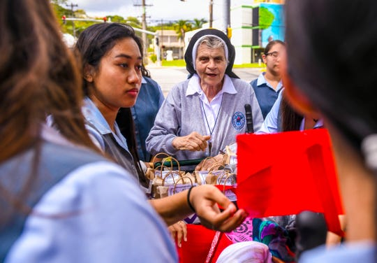 Sister Dorothy Lettiere organizes a group of Academy of Our Lady Guam students as they distribute clothing and supplies to members of Hagåtña's homeless population during a weekly outreach stroll on Dec. 5, 2019.
